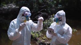 Två män i biohazard passar provtagningvatten fotografering för bildbyråer