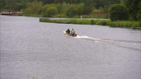 Två män i en liten snabb motorbåt kör bort lager videofilmer