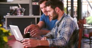 Två män i kafét som tillsammans arbetar på bärbara datorn lager videofilmer