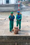Två män i säkerhetshjälmar, västar och funktionsduglig kläder Fotografering för Bildbyråer
