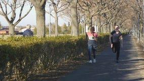 Två män konkurrerar i spring för en kort avståndshastighet Segrar för svart grabb framåt av caucasianen lager videofilmer