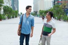 Två män ler tala det utomhus- asiatiska blandningloppet Royaltyfri Foto