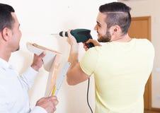 Två män med drillborren och nivån fotografering för bildbyråer