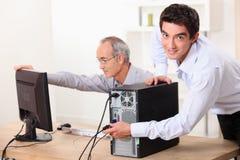 Två män med en dator royaltyfri bild