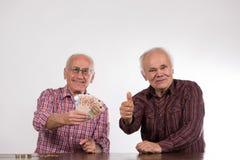 Två män med euroanmärkningar s i deras händer royaltyfri fotografi
