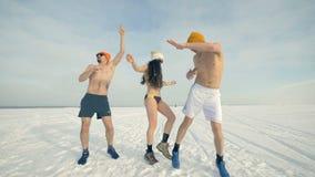 Två män och en kvinna i bikini dansar på snön 4K arkivfilmer