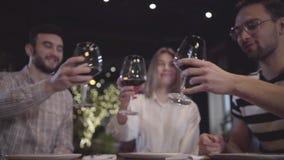 Två män och kvinna som klirrar deras glases med rött vin som sitter på tabellen i modern turkisk restaurang Vänner har lager videofilmer