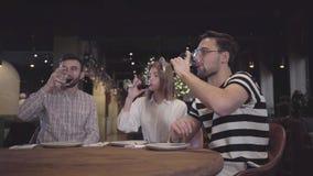Två män och kvinna som klirrar deras glases med rött vin som sitter på tabellen i modern turkisk restaurang Vänner har arkivfilmer