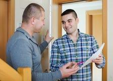 Två män på lägenhettröskeln Arkivbild