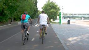 Två män rider att cykla för berg i parkerar längs en hängiven bana arkivfilmer