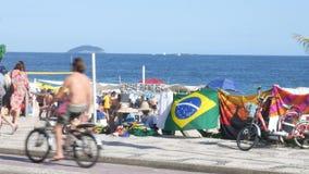 Två män säljer hattar och strandtillbehör till turister på Rio de Janeiro den iconic Ipanema stranden stock video