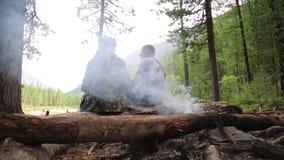 Två män sitter på rakningen nära branden stock video
