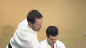 Två män som öva Aikido i idrottshallen stock video
