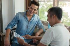 Två män som använder minnestavlan, asiatiska grabbar för blandningloppvänner Royaltyfri Bild