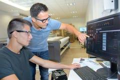 Två män som bär anblickar som ser datorskärmen royaltyfria foton
