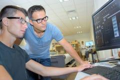 Två män som bär glasögon som ser datorskärmen arkivfoton