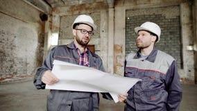 Två män, som byggmästare i en skyddande hjälm på deras huvud och speciala kläder ser fabriksbyggnaden för att lager videofilmer