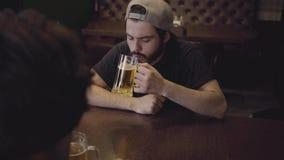 Två män som dricker öl som sitter på en tabell i en bar r lager videofilmer