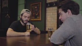 Två män som dricker öl som sitter på en tabell i en bar r arkivfilmer