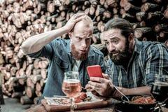 Två män som förvånas på nyheterna dem som ser på en smartphone arkivfoto