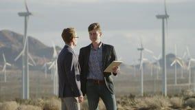 Två män som gör ett avtal nära väderkvarnarna stock video