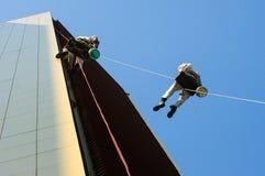 Två män som högt arbetar på ett rep Arkivfoto