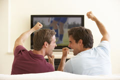 Två män som hemma håller ögonen på Widescreen TV royaltyfri bild