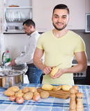 Två män som hemma lagar mat royaltyfri foto