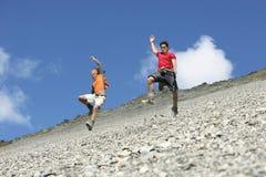 Två män som hoppar ner stenrasfält Royaltyfria Bilder