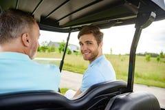Två män som kör vagnen på golfbana Fotografering för Bildbyråer