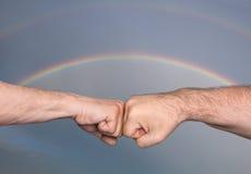 Två män som knuffar till nävar arkivfoto