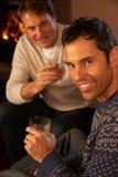 Två män som kopplar av att sitta på dricka Whisky för Sofa Royaltyfri Fotografi