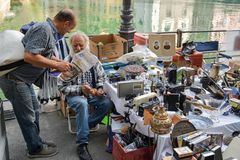 Två män som läser tidningen bredvid en av ställningarna med antikviteten i den traditionella lördag marknaden i Luzern arkivfoto