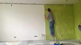Två män som målar en vägg med rullen stock video