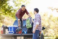 Två män som packar upp, väljer upp lastbilen på campa ferie Royaltyfri Foto