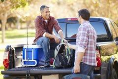 Två män som packar upp, väljer upp lastbilen på campa ferie Royaltyfri Bild
