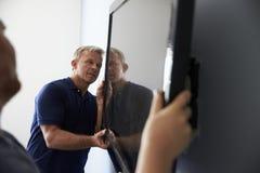 Två män som passar television för plan skärm till väggen royaltyfria foton