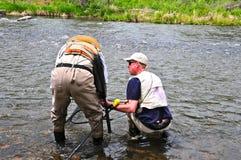 Två män som pratar på floden royaltyfri fotografi