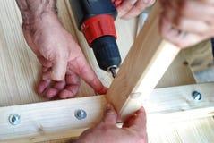 Två män som reparationr trä fotografering för bildbyråer
