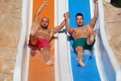 Två män som rider ner glidbana-vänner för ett vatten som tycker om ett vattenrör, rider Arkivbilder