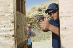 Två män som siktar handvapen på skjutavstånd arkivbild