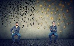 Två män som sitter bredvid de en, har många frågor en andra många ljusa idéer arkivbild