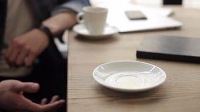 Två män som sitter i kafét som dricker kaffe arkivfilmer