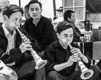 Två män som spelar det traditionella musikinstrumentet i en lokal marknad, Sapa, Vietnam royaltyfri bild