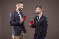 Två män som står med en kopp kaffe royaltyfri fotografi