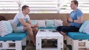 Två män som talar i ett kafé stock video