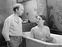 Två män som talar medan en som sitter i ett badkar (alla visade personer inte är längre uppehälle, och inget gods finns Leverantö Royaltyfri Bild