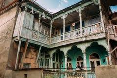 Två män som talar, medan stå på balkongen av ett gammalt hus in Arkivfoto