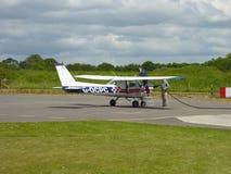 Två män som tankar ett ljust flygplan Royaltyfri Fotografi