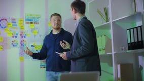 Två män står på kontoret nära ett bräde med anmärkningar stock video